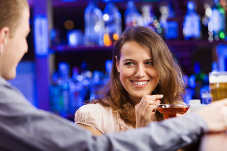 Young couple in bar having drinks and talking photo