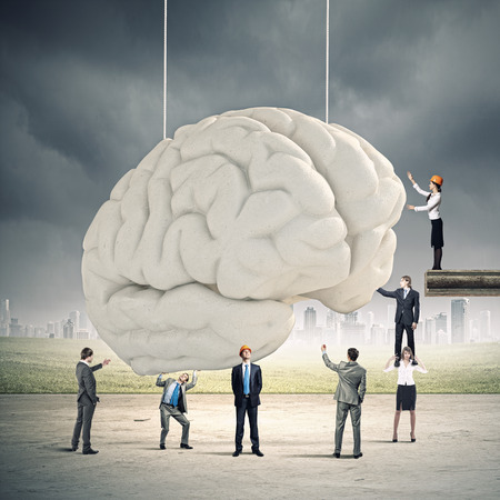 Huge human brain and many little businesspeople around photo