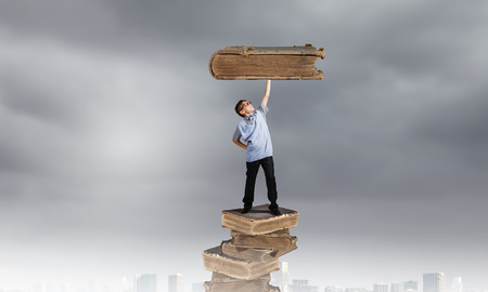 Young man holding huge book above head on one hand photo