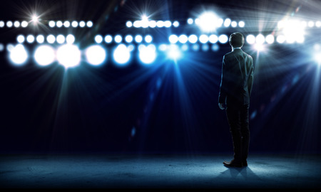 concert stage: Rear view of businessman standing in lights of stage
