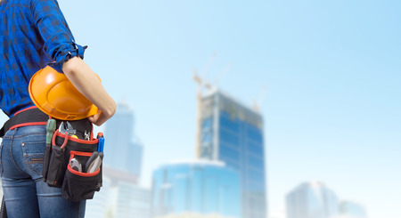 Close up of woman mechanic with yellow helmet in hand against city background photo