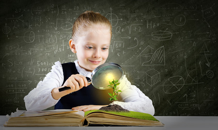 Schoolgirl examining opened book with magnifying glass photo