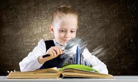 schoolkid search: Colegiala examinar libro abierto con lupa Foto de archivo
