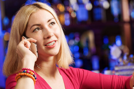 lady on phone: Young attractive lady at bar talking on phone Stock Photo