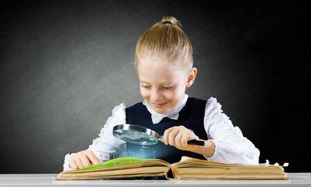 niños estudiando: Colegiala examinar libro abierto con lupa Foto de archivo