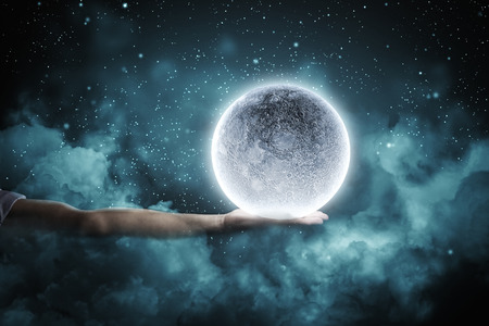 Close up of human hand holding blue glowing moon Stock Photo