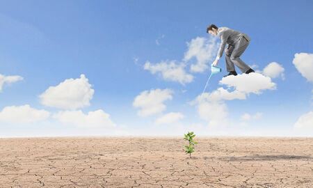 Young businessman standing on cloud and watering sprout