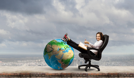 Young businesswoman sitting in chair and reading book  Elements of this image are furnished by NASA photo