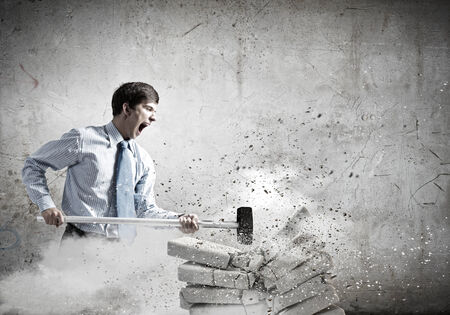 Young angry businessman crashing bricks with hammer photo