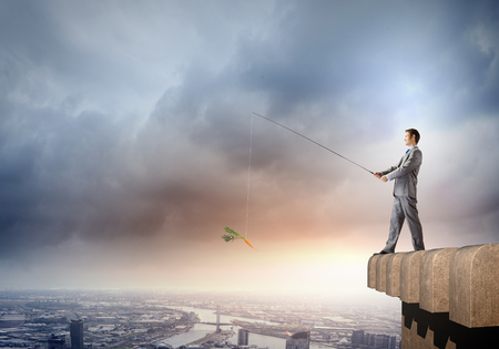 Businessman standing on top of building and fishing with rod photo