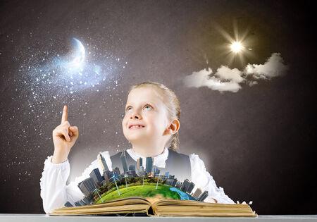 schoolkid search: Colegiala mirando en el libro abierto elementos de esta imagen proporcionada por la NASA est�n