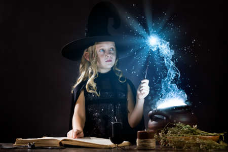 Little Halloween witch reading conjure above pot photo