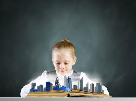schoolkid search: Chica de la escuela linda que mira en el libro abierto con el modelo de ciudad