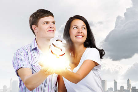 Young happy couple holding dollar sign in palms photo