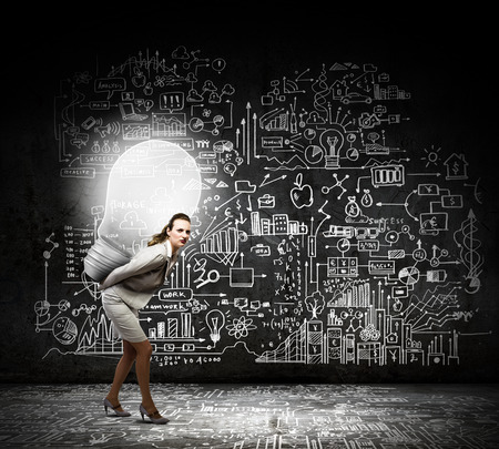 Young businesswoman carrying light bulb on back photo
