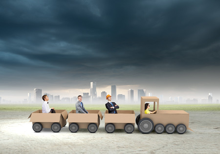 Young business people riding carton train  Teamwork concept photo
