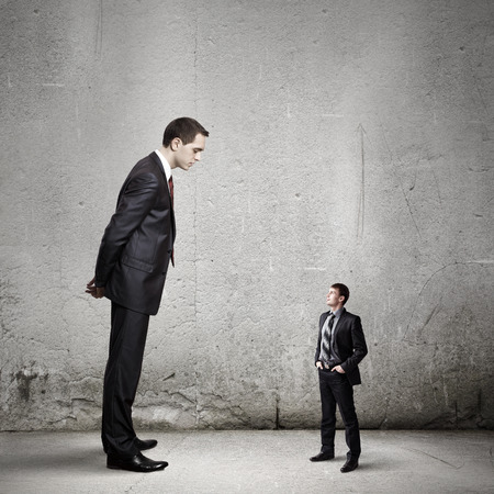 Big bossy businessman looking down at small businessman Stock Photo - 29178511