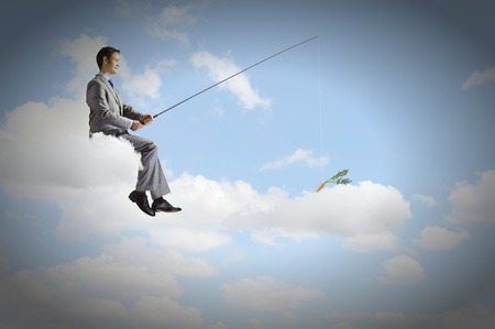 Businessman sitting on cloud and fishing with rod photo