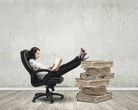 Young businesswoman sitting in chair and reading book photo