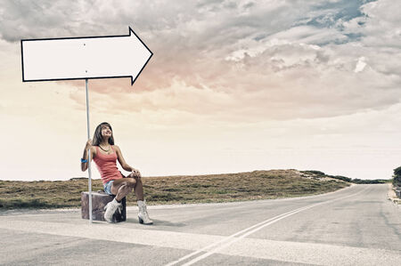 Young pretty girl traveler sitting on suitcase aside of road photo