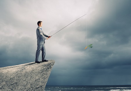 Businessman sitting on rock and fishing with rod photo