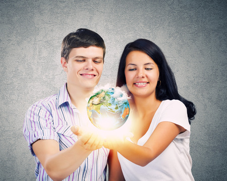 Young happy couple holding earth planet in palms  Elements of this image are furnished by NASA photo