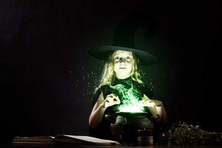 conjure: Little Halloween witch reading conjure above pot
