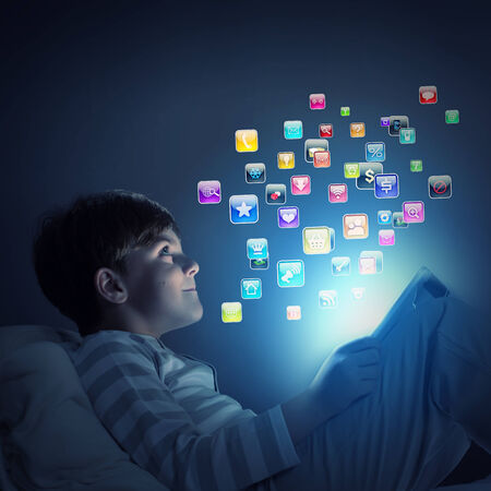 parental control: Cute little boy sitting in bed and using tablet pc