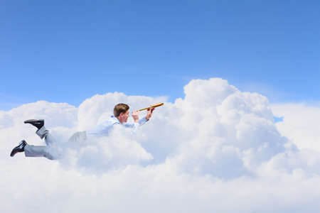 Young businessman flying in sky and lokking in spyglass photo