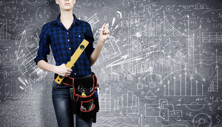 Young woman mechanic with ruler in hand against city background photo