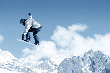 Snowboarder making jump high in clear sky photo