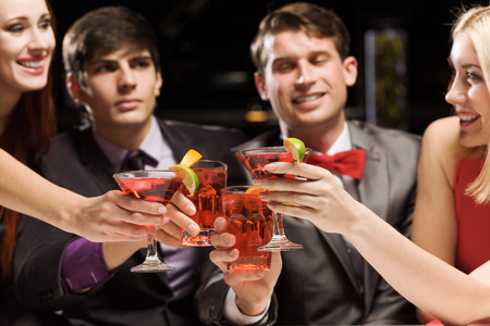 Young attractive people of four having cocktail party photo