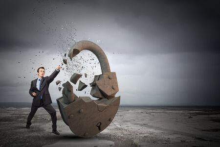 Businessman breaking stone lock with karate kick photo