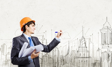 Young man engineer drawing sketches of construction project photo