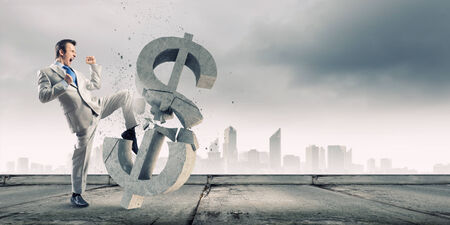 Businessman breaking stone dollar symbol with karate punch photo