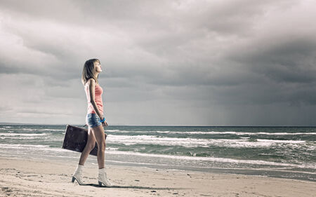 Young woman tourist walking with suitcase at seaside photo
