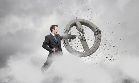 Angry determined businessman crashing stone prohibition symbol photo