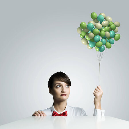 Young woman holding bunch of colorful balloons photo