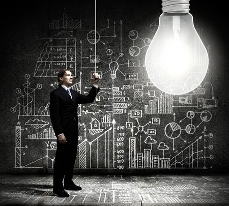 Businessman switching on light bulb with business sketches at background photo