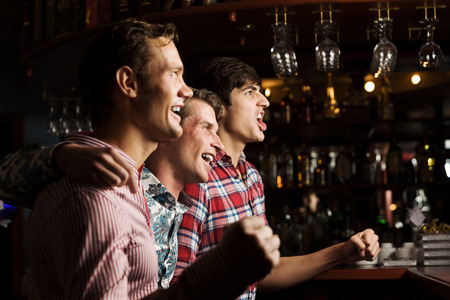 cheering fans: Three young men at bar watching match and shouting