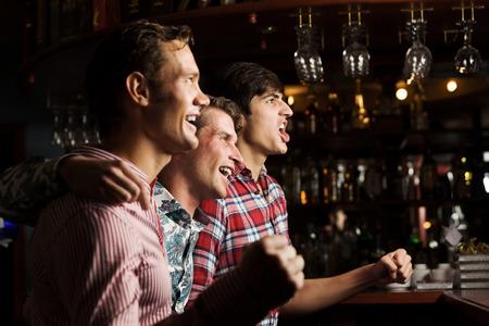 bares: Tr�s jovens no bar assistindo jogo e gritando