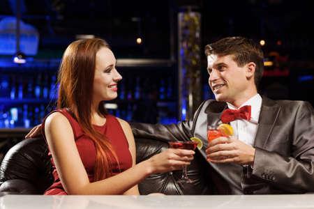 vergezeld: Jonge knappe man in het restaurant begeleid door elegante dame Stockfoto