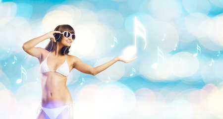 Young attractive girl in bikini wearing headphones touching media icon photo