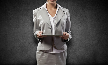 Young pretty businesswoman against grey background using tablet pc photo