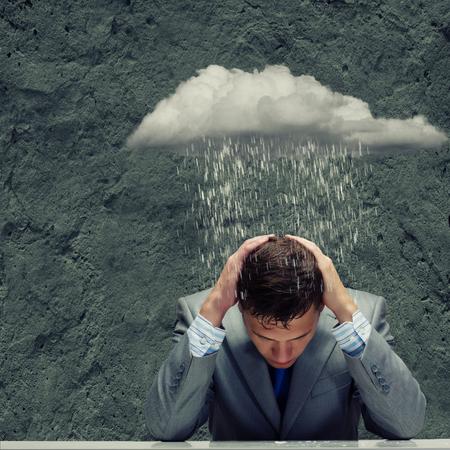 Depressed young businessman sitting wet under rain photo