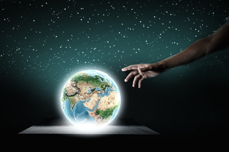 Close up of human hand touching Earth planet with finger