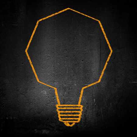 Conceptual image of light bulb on black wall photo
