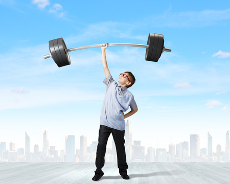 Cute boy of school age lifting barbell above head photo