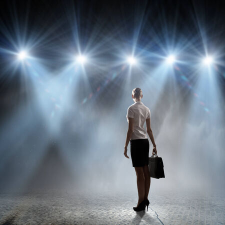 Rear view of businesswoman standing in lights of stage Stock Photo