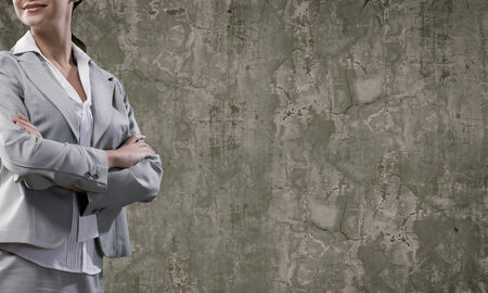 Chest view of businesswoman in suit against cement wall photo